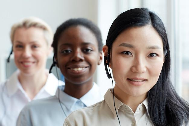 Grupo multiétnico de operadoras de call center em pé na fila, foco em mulher asiática sorridente usando fone de ouvido em primeiro plano