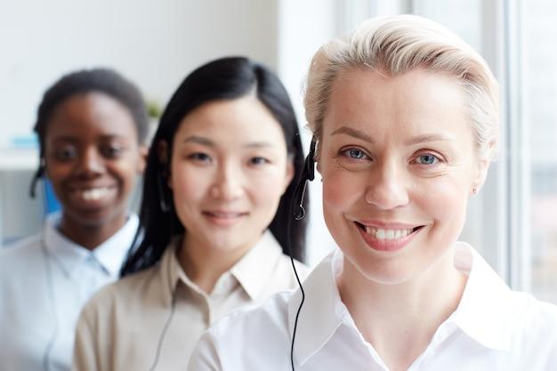 Grupo multiétnico de operadoras de call center em pé na fila, foco em mulher loira sorridente usando fone de ouvido em primeiro plano