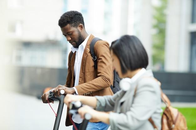 Grupo multiétnico de pessoas andando de scooter elétrico