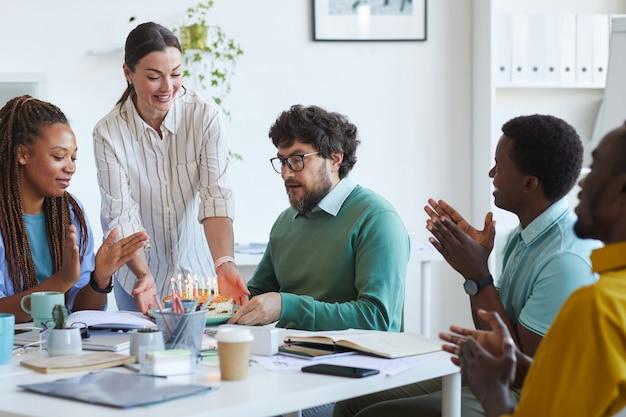 Grupo multiétnico de pessoas comemorando aniversário no escritório, foco na mulher sorridente trazendo bolo para um colega barbudo