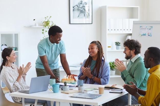 Grupo multiétnico de pessoas comemorando aniversário no escritório, foco no jovem sorridente trazendo bolo para uma mulher afro-americana