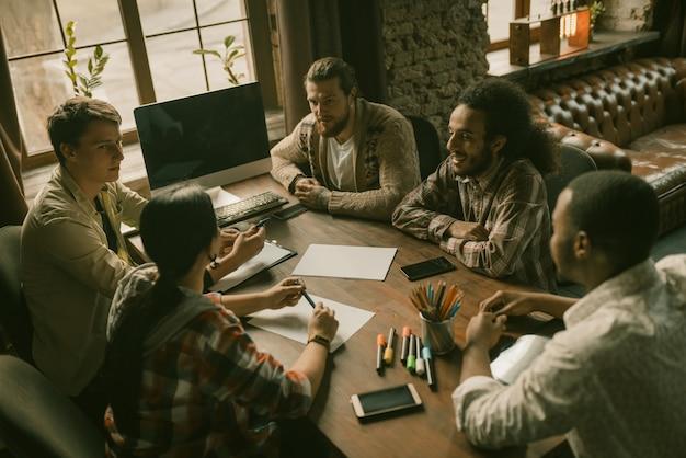 Grupo multiétnico de pessoas criativas tem tempo de brainstorming