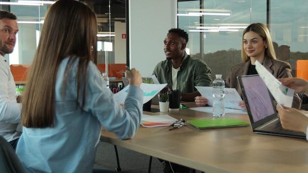 Grupo multiétnico de pessoas na equipe de negócios criativos de um escritório moderno trabalhando juntos em um projeto, rindo e sorrindo