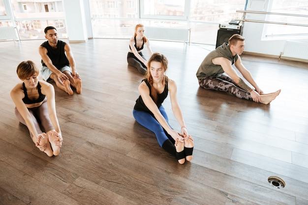 Grupo multiétnico de pessoas que se estendem no estúdio de yoga