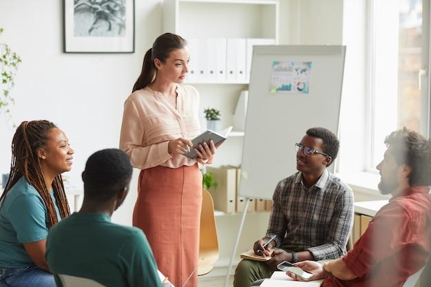Grupo multiétnico de pessoas sentadas em círculo enquanto discutem estratégia para projeto de negócios no escritório, foco na gerente feminina dando instruções