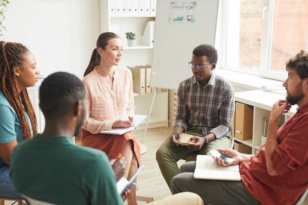 Grupo multiétnico de pessoas sentadas em círculo enquanto discutem estratégia para projeto de negócios no escritório, foco na líder feminina conversando com colegas