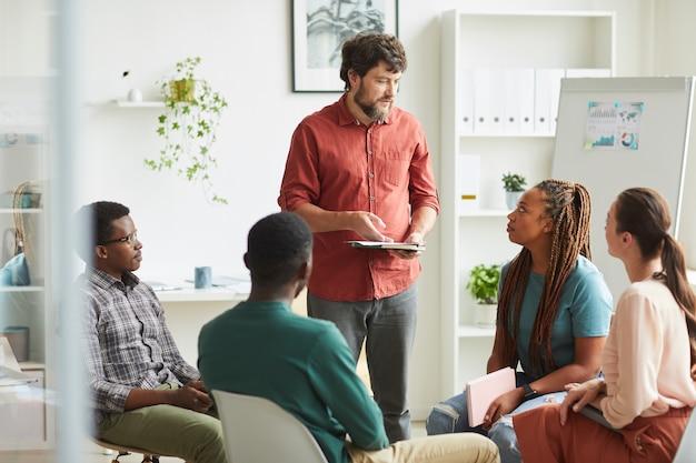 Grupo multiétnico de pessoas sentadas em círculo enquanto discutem o projeto de negócios no escritório, foco no gerente sorridente e aclamado falando com os colegas