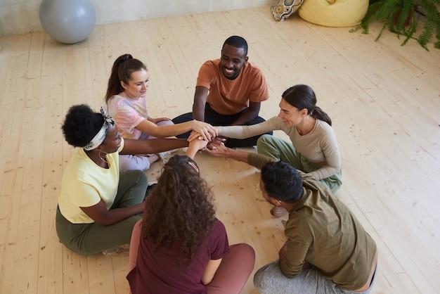 Grupo multiétnico de pessoas sentadas no chão em círculo e de mãos dadas durante as aulas