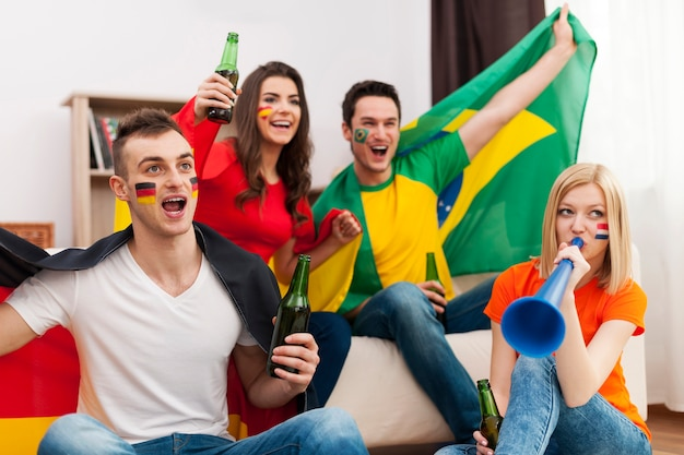 Grupo multiétnico de pessoas torcendo por uma partida de futebol