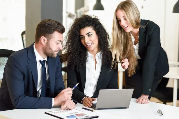 Grupo multiétnico de três empresários reunidos em um escritório moderno. duas mulheres e um homem caucasiano vestindo um terno olhando para um computador laptop.