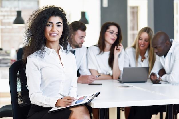Grupo multiétnico de três empresários reunidos em um moderno o