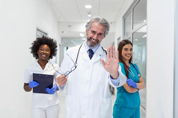 Grupo multiétnico de três médicos e enfermeiras em pé no corredor de um hospital, vestindo jalecos e jalecos.