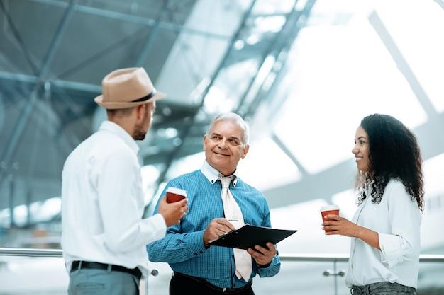 Grupo multinacional de empresários discutindo documentos de negócios