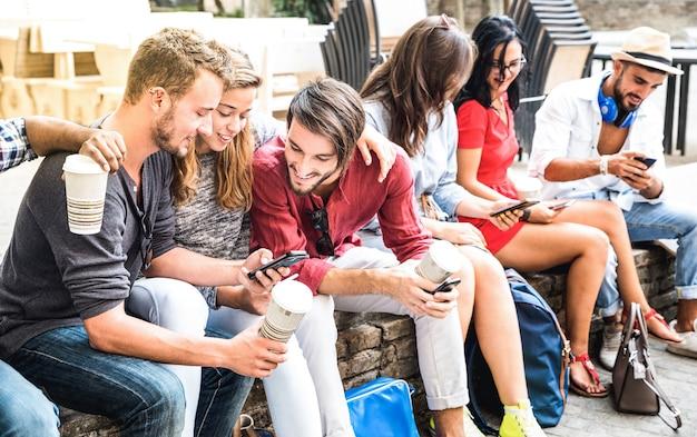 Grupo multirracial da geração y usando smartphone no quintal de uma faculdade da cidade