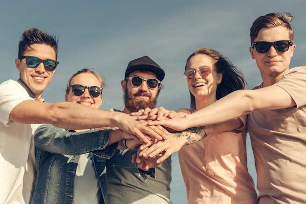 Grupo multirracial de amigos com as mãos na pilha