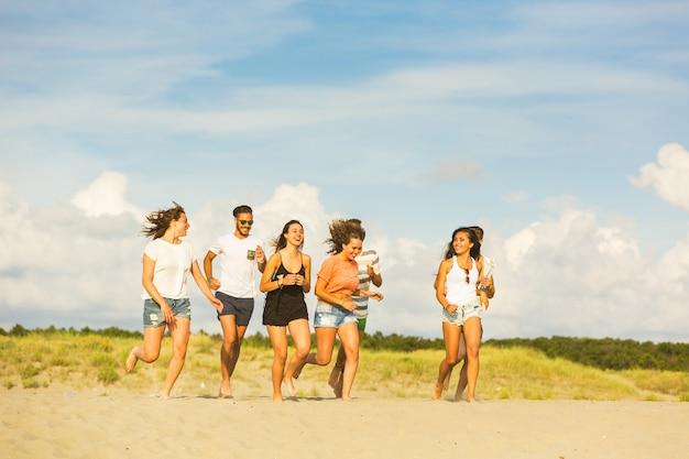Grupo multirracial de amigos correndo na praia