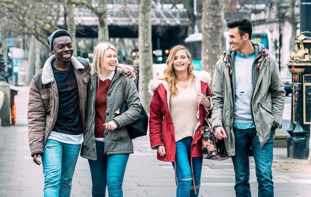 Grupo multirracial de amigos milenares andando no centro da cidade de londres