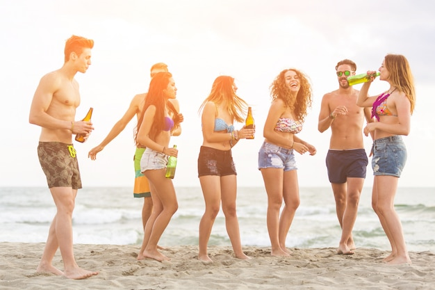 Grupo multirracial de amigos, uma festa na praia
