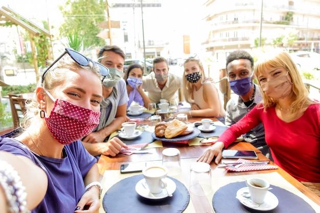 Grupo multirracial de amigos usando máscara de proteção no restaurante