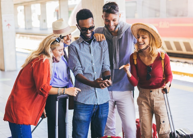 Grupo multirracial de amigos usando máscara facial usando smartphone na estação ferroviária