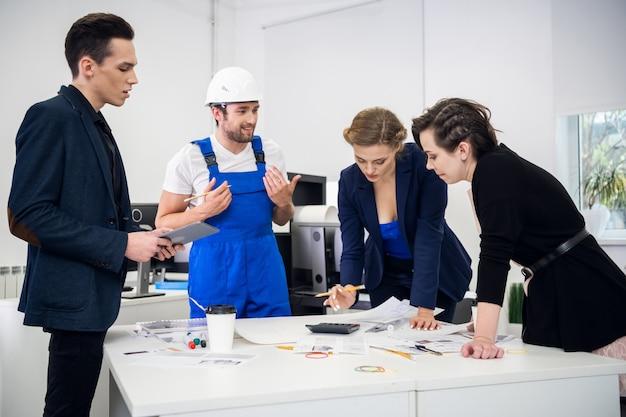 Grupo multirracial de construtores, construtores, engenheiros e arquitetos discutindo uma planta no escritório