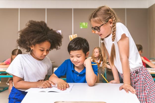 Grupo multirracial de crianças na escola primária - alunos brincalhões aproveitando o tempo da escola e as aulas com o professor e colegas de classe