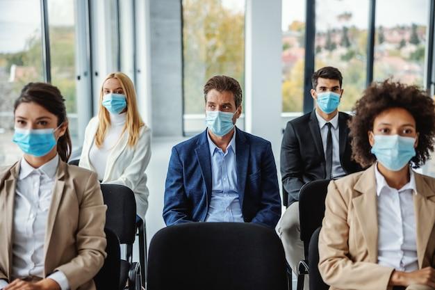 Grupo multirracial de empresários com máscaras, sentado no seminário durante o vírus corona.