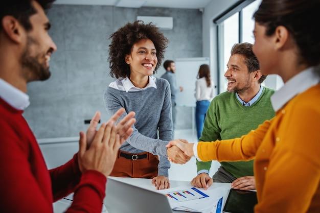 Grupo multirracial de empresários, tendo reunião na sala de reuniões. parceiros de negócios de duas mulheres apertando as mãos.