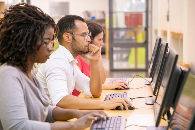 Grupo multirracial de estudantes treinando na aula de informática