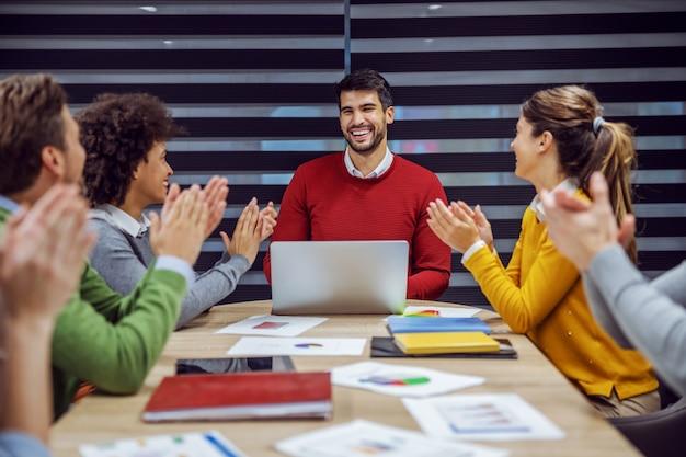 Grupo multirracial de executivos sentados no escritório e em reunião