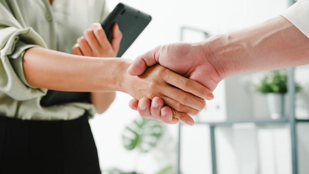 Grupo multirracial de jovens criativos em roupas casuais inteligentes discutindo negócios, apertando as mãos juntos