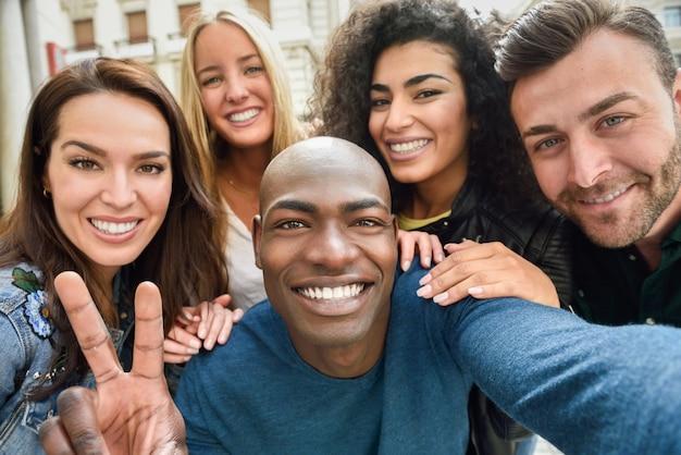 Grupo multirracial de jovens que tomam selfie