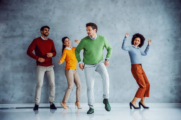 Grupo multirracial lúdico de executivos dançando.