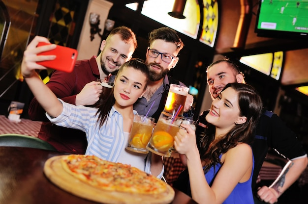 Grupo ou companhia de jovens - amigos bebem cerveja, comem pizza, conversam e riem e tiram selfie na câmera do smartphone na superfície do bar