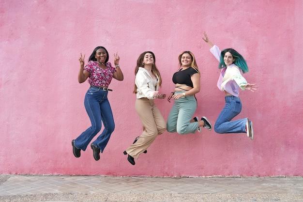 Grupo quatro lindas amigas multiétnicas pulando felizes