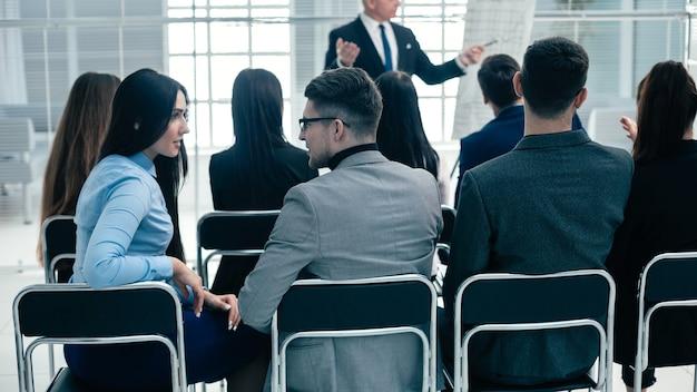 Grupo retrovisor de funcionários sentados na sala de conferências