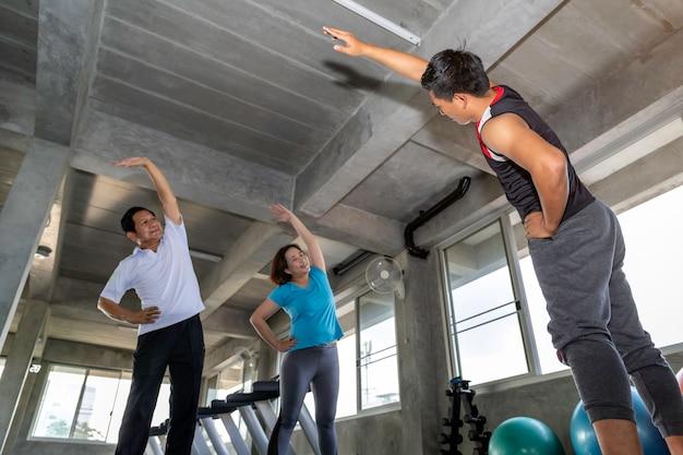 Grupo sênior alongamento atraente no ginásio de fitness.