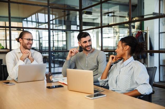 Grupo sorridente de colegas sentados no centro, trabalhando com laptops