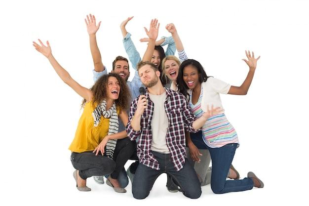 Grupo sorridente de jovens amigos se divertindo fazendo karaoke