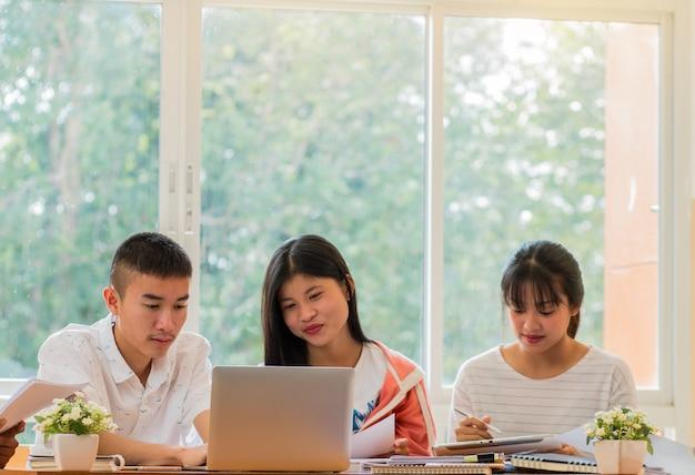 Grupos asiáticos de estudantes universitários usando laptop
