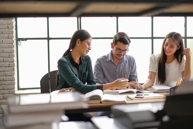 Grupos asiáticos são de brainstorming, trabalhando no escritório