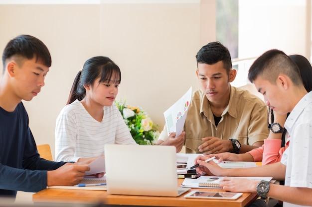 Grupos de estudantes do asian college usando laptop, tablet, estudando junto com cadernos