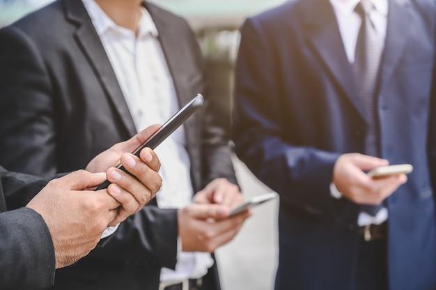 Grupos de negócios estão usando telefones celulares para fazer contatos comerciais, comércio, comunicações, ações, finanças, tecnologia.