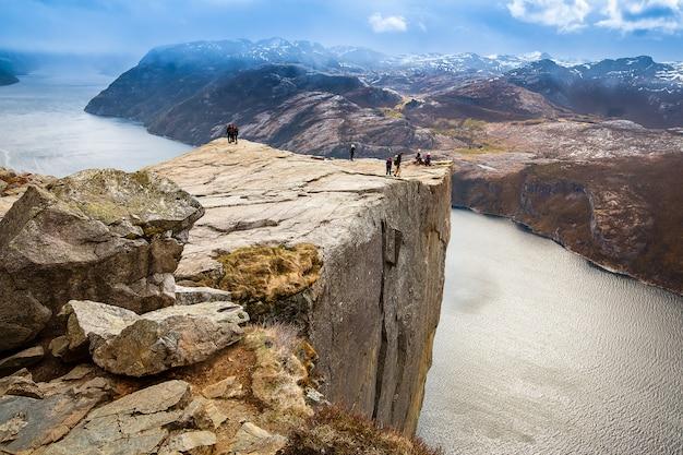 Grupos de turistas em pé na borda da rocha do púlpito (preikestolen)