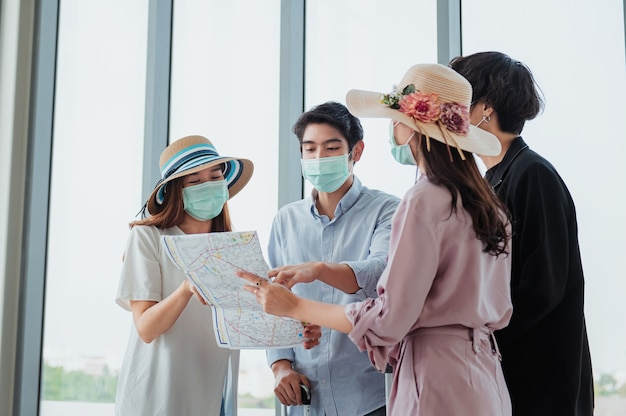 Grupos de turistas usam máscaras e olham mapas no aeroporto antes de viajar.