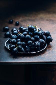 Grupos de uvas vermelhas maduras frescas em um fundo estrutural da tabela da bandeja do metal. uvas escuras, uvas azuis