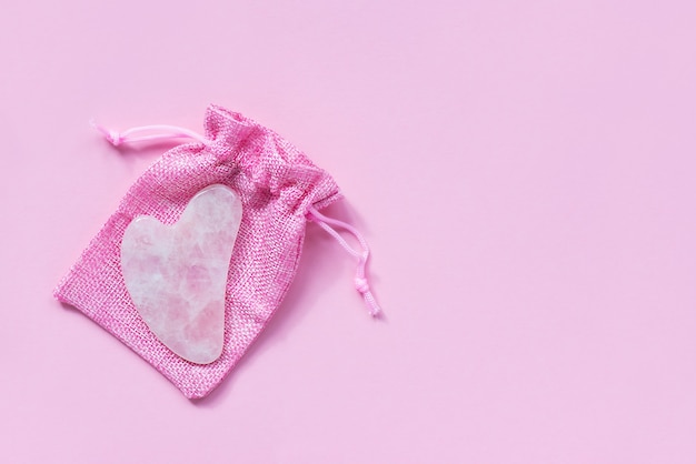 Gua sha de quartzo rosa em uma bolsa rosa