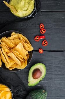 Guacamole caseiro e molho de queijo com nachos, em mesa de madeira preta, vista de cima ou plano