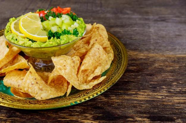 Guacamole com microplaquetas de tortilla em uma bacia em um fundo de madeira escuro. vista superior com espaço de cópia.