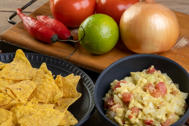 Guacamole com tortilhas com ingredientes no fundo.